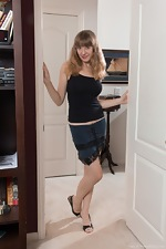 Dani strips naked by her white door