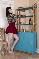 Little Olive models by her blue sideboard